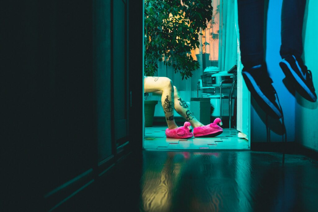 Girl wearing pink slippers while a body hangs from the ceiling